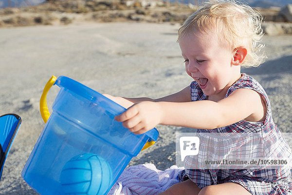 Happy female toddler playing on beach with toy bucket