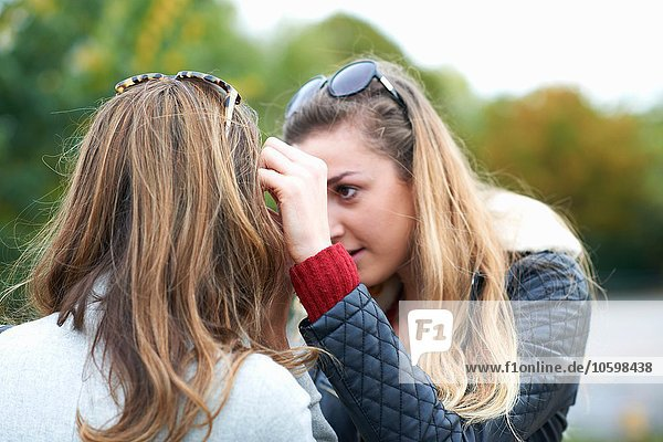 Young woman brushing hair from friend's face  rear view