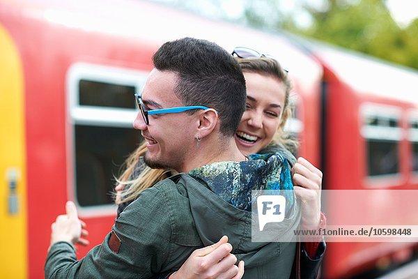 Heterosexual couple hugging at railway station  smiling