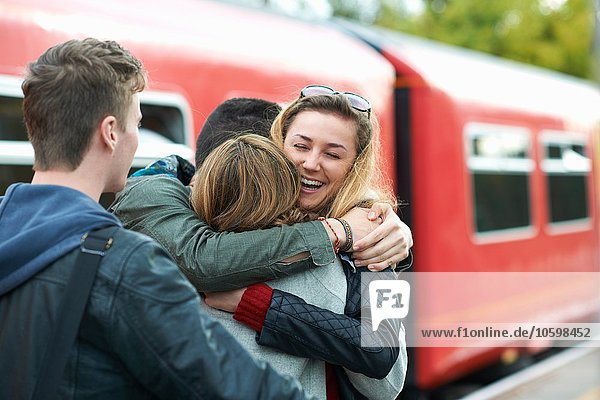 Group of friends hugging at railway station  smiling