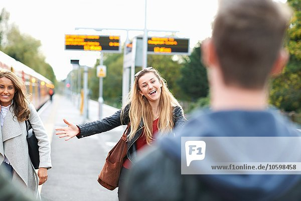 Young woman  with arms open  greeting young man  at railway station