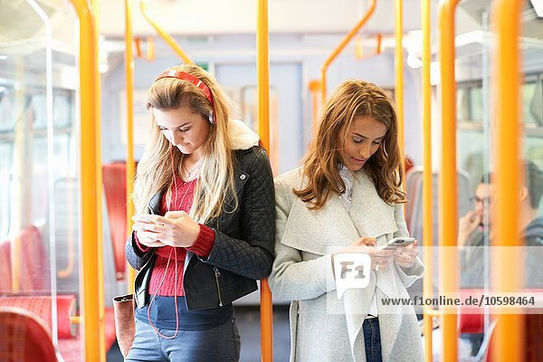 Two young women on train  back to back  using smartphones
