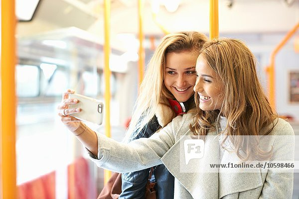 Two young female friends on train  taking self portrait  using smartphone