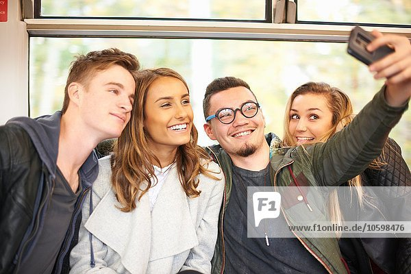 Group of young friends on train  taking self portrait  using smartphone