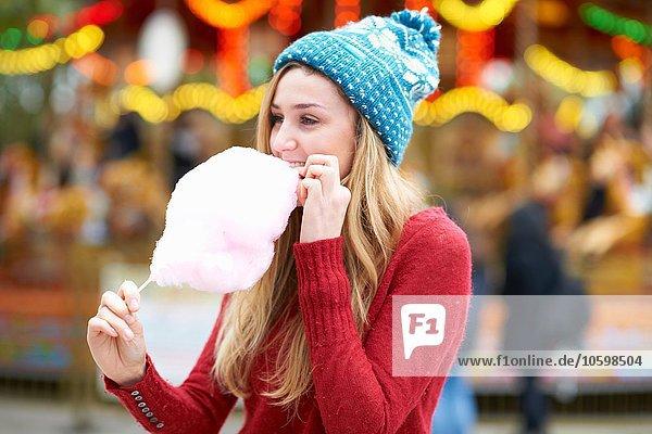 Junge Frau isst Zuckerwatte auf der Kirmes  im Freien Junge Frau isst Zuckerwatte auf der Kirmes, im Freien