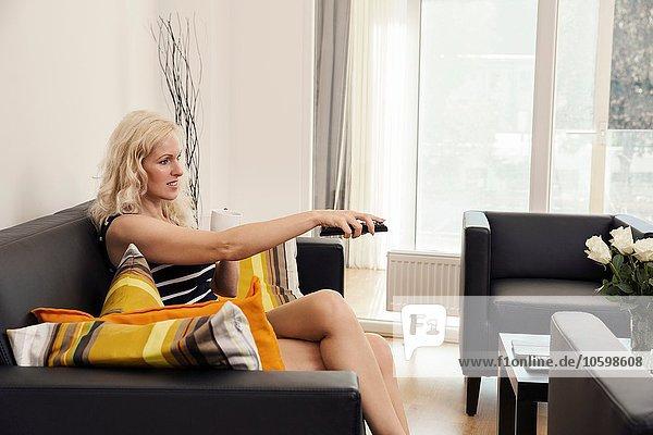 Seitenansicht einer reifen Frau  die auf dem Sofa sitzt und lächelnd wegsieht.