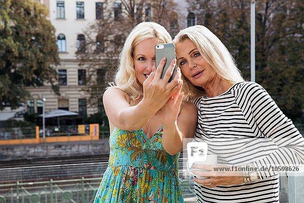 Frauen im Freien mit dem Smartphone zu nehmen Selfie lächeln