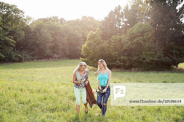 Vorderansicht von Frauen mit Picknickdecke und Blumen  die lächelnd über die Feldlandschaft gehen.