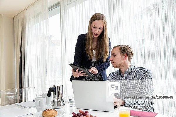 Junge Frau zeigt Kollegin digitales Tablett beim Frühstücks-Business-Meeting