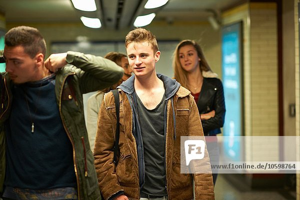 Four young adult friends walking through London underground station  London  UK