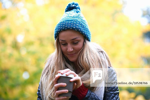 Young woman removing lid from takeaway coffee in park