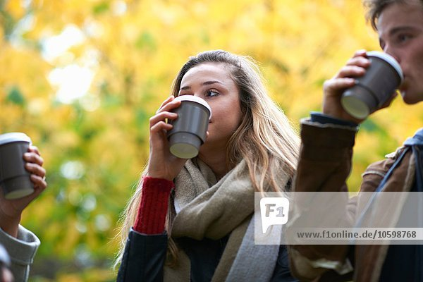 Young adult friends drinking takeaway coffee in autumn park