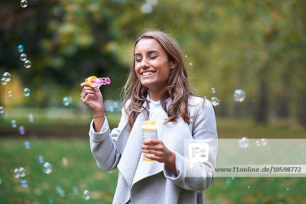 Young woman blowing bubbles in autumn park