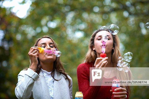 Zwei junge Freundinnen blasen Blasen im Park