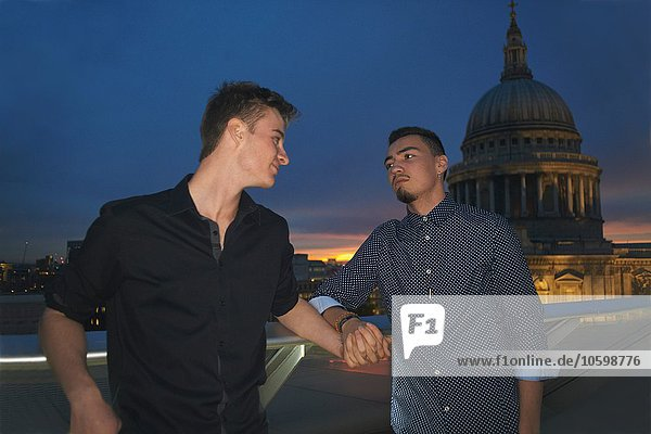 Two young men holding hands in front of St Pauls at night  London  UK