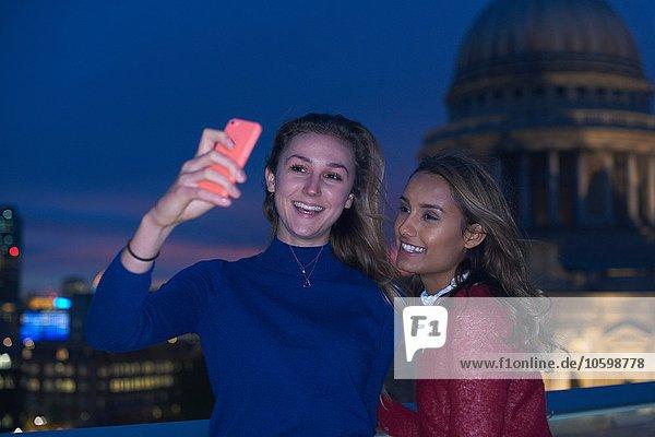Zwei junge Frauen mit Smartphone-Selfie vor St. Pauls bei Nacht,  London,  UK