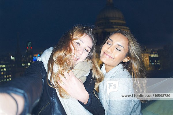 Two young women taking selfie in front of St Pauls at night  London  UK