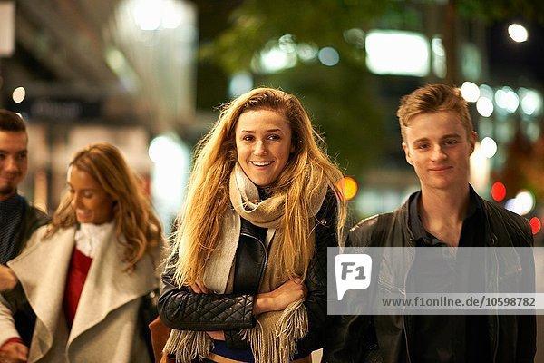 Zwei junge Paare schlendern Arm in Arm entlang der Straße bei Nacht  London  UK