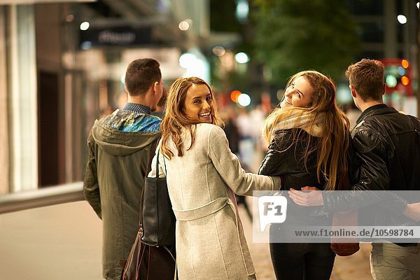 Rear view of two young couples strolling arm in arm along street at night  London  UK