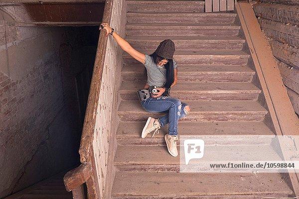 Junge Fotografin beim Vorbereiten der Kamera auf der Treppe im alten Industriegebäude