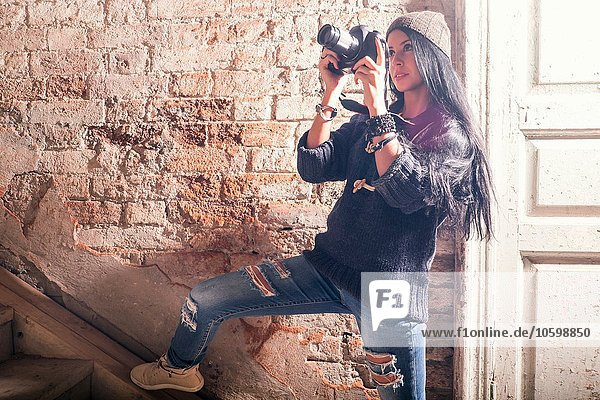 Young female photographer photographing stairs in old industrial building
