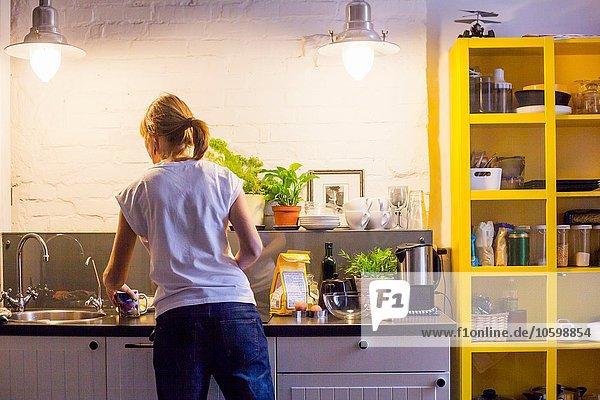 Rückansicht der mittleren erwachsenen Frau beim Backen am Küchentisch