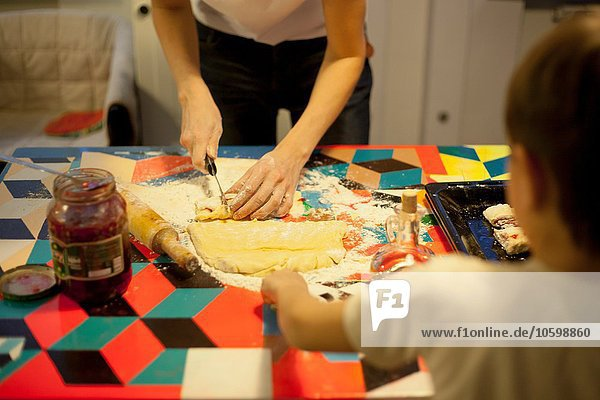 Frau und Sohn beim Teigschneiden am Küchentisch