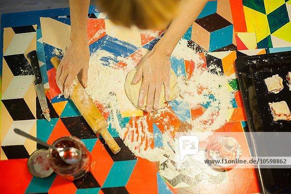 Draufsicht auf die Hände der Frauen  die den Teig am Küchentisch platt machen.