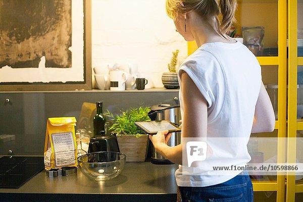 Mittlere erwachsene Frau liest Rezept auf digitalem Tablett am Küchentisch