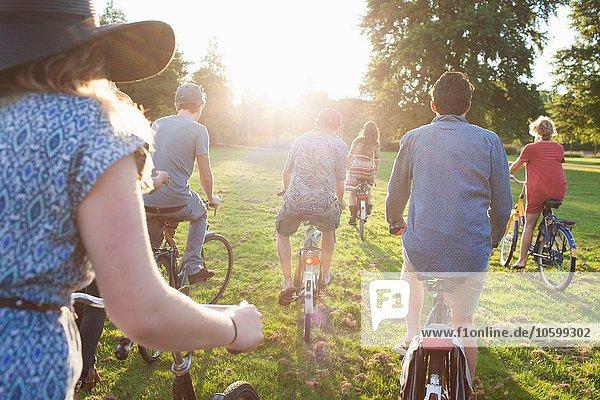 Rückansicht der im Park ankommenden Erwachsenen mit Fahrrädern bei Sonnenuntergang