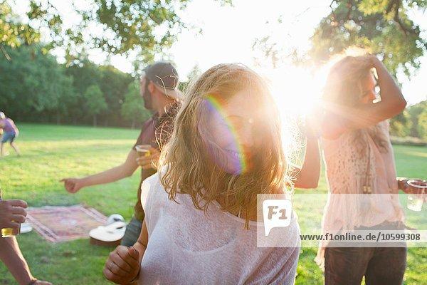 Erwachsene Freunde beim Plaudern auf der Party im Park bei Sonnenuntergang