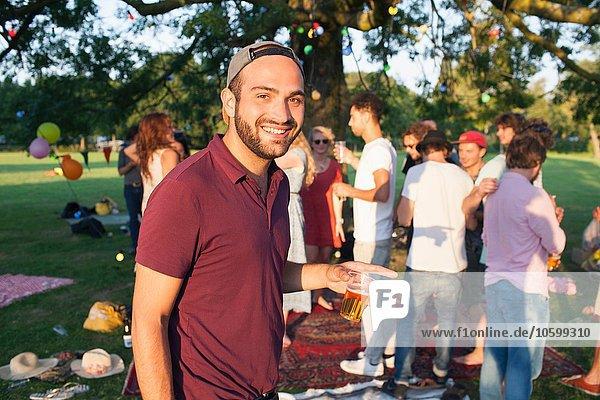 Porträt eines jungen Mannes auf einer überfüllten Party im Park bei Sonnenuntergang