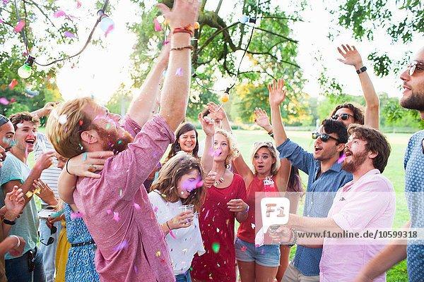 Erwachsene feiern mit erhobenen Armen bei Sonnenuntergangsparty im Park