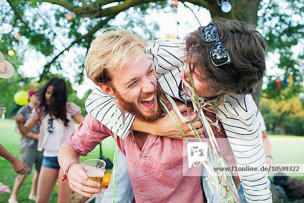 Zwei männliche erwachsene Freunde in Luftschlangen gehüllt  die sich bei Sonnenuntergang im Park umarmen.