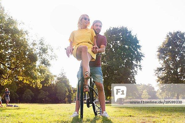 Junges Paar auf dem Fahrrad bei Sonnenuntergang im Park