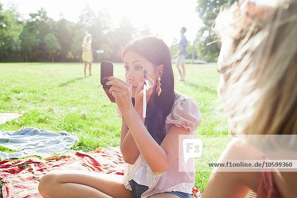 Weibliche Freunde  die sich auf der Parkparty schminken.