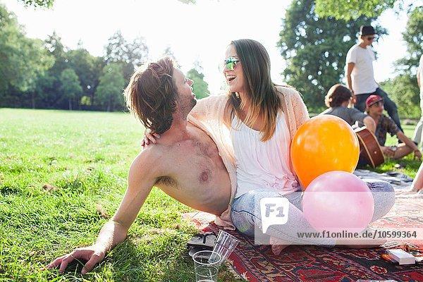 Junges Paar flirtet auf der Parkparty