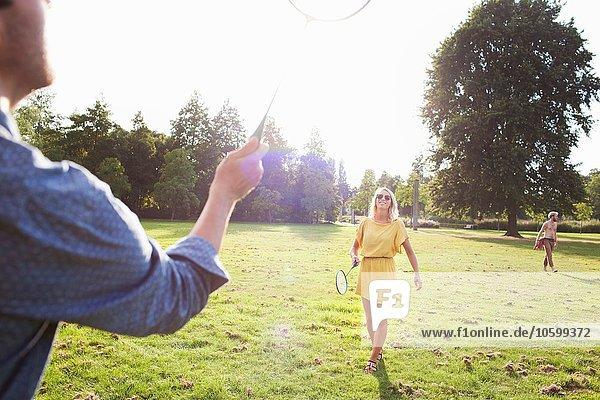 Junges Paar spielt Badminton im sonnigen Park