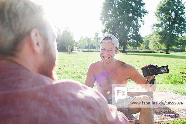 Junge Männer beim Fotografieren auf der Parkparty