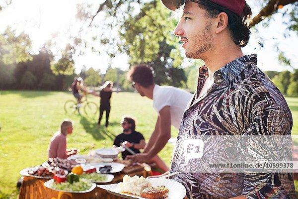 Junger Mann mit Picknickteller auf der Parkparty