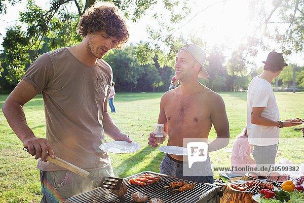 Junge Männer grillen auf der Sunset Park Party
