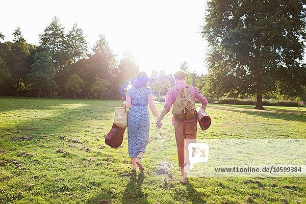 Rückansicht des romantischen jungen Paares mit Teppich im Park
