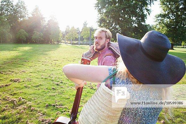 Romantisches junges Paar mit Teppich zum Picknick im Park