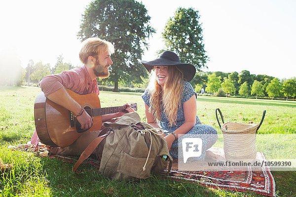 Romantisches junges Paar spielt Akustikgitarre im Park