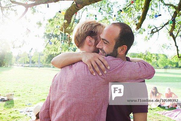 Zwei junge Männer umarmen sich auf einer Party im Park.