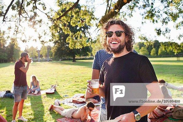 Porträt eines jungen Mannes beim Biertrinken bei einem Gruppen-Picknick im Park
