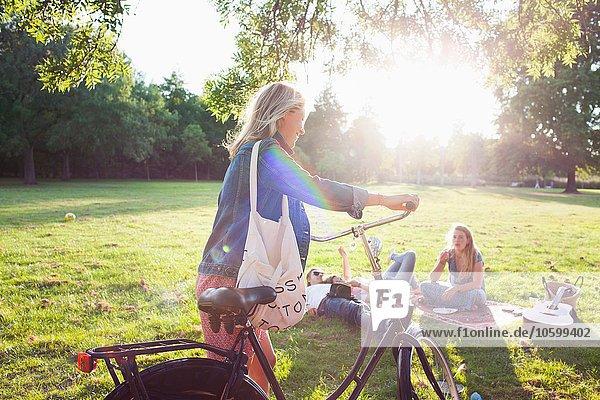 Junge Frau kommt mit dem Fahrrad zur Sunset Park Party