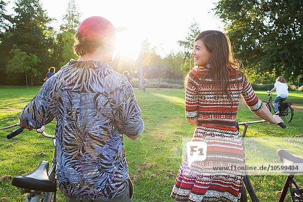 Rückansicht des Partypaares  das mit dem Fahrrad zur Sunset Park Party anreist.
