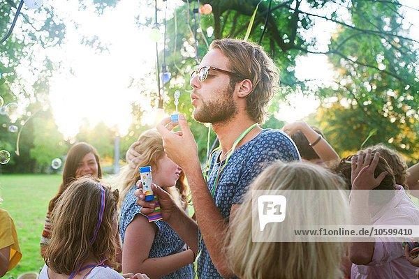 Junger Mann bläst Blasen auf Gruppenparty im Park bei Sonnenuntergang