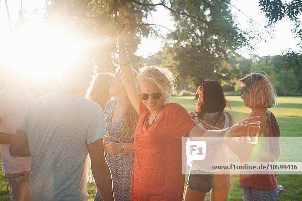 Erwachsene Freunde beim Tanzen und Trinken im Park bei Sonnenuntergang